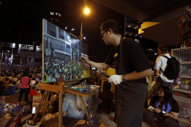 A man paints the scene of protesters and riot police during a rally attended by thousands in front of the government headquarters in Hong Kong September 27, 2014. (Photo by Bobby Yip/Reuters)