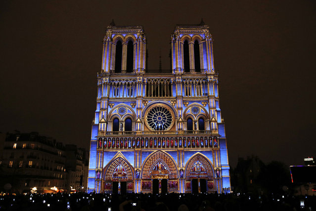 """The Notre Dame cathedral is illuminated during a light show called """"Dame de Coeur"""" to celebrate the centenary of the First World War, in Paris, Wednesday, November 8, 2017. (Photo by Christophe Ena/AP Photo)"""