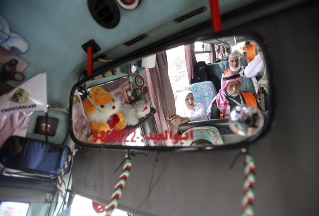 Palestinians are reflected in a rear-view mirror while sitting in a bus before leaving for the annual Hajj pilgrimage in Mecca, at Khan Younis in the southern Gaza Strip September 18, 2014. (Photo by Ibraheem Abu Mustafa/Reuters)
