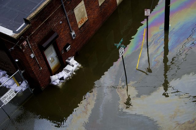 A street and business are flooded in Hoboken, NJ. (Photo by Charles Sykes/Associated Press)
