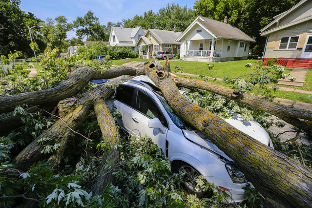 A car is crushed by a felled tree in Omaha, Neb., Wednesday, August 24, 2016, as thunderstorms have lashed several parts of eastern Nebraska, leaving thousands of people without power and some stranded by street flooding and storm debris. (Photo by Nati Harnik/AP Photo)