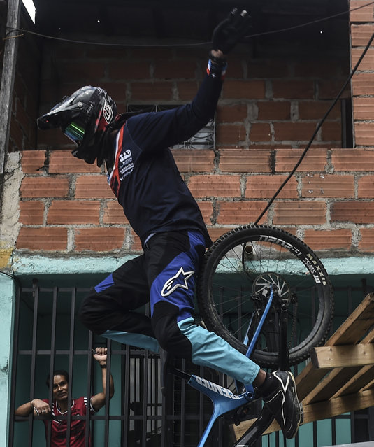A resident looks at a downhill rider during the Urban Bike Inder Medellin race final at the Comuna 1 shantytown in Medellin, Antioquia department, Colombia on November 19, 2017. (Photo by Joaquin Sarmiento/AFP Photo)