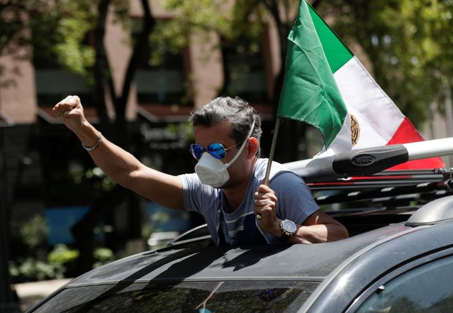 A man holds a Mexican flag from a vehicle during a caravan to protest against Mexico's President Andres Manuel Lopez Obrador, as the spread of the coronavirus disease (COVID-19) continues, in Mexico City, Mexico June 28, 2020. (Photo by Henry Romero/Reuters)