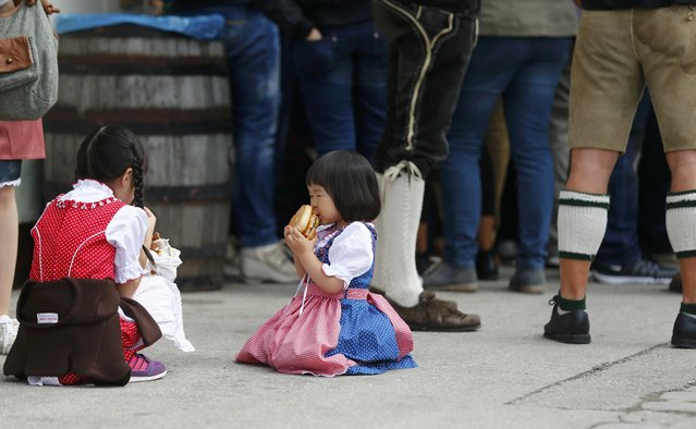 Girls sit on the floor as they eat during the first day of the 182nd Oktoberfest in Munich, Germany, September 19, 2015. (Photo by Michael Dalder/Reuters)