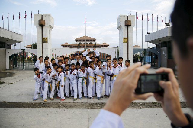 A group of taekwondo students pose for a picture in front of the parliament during a nationwide strike, called by the opposition parties against the proposed constitution in Kathmandu, Nepal September 20, 2015. (Photo by Navesh Chitrakar/Reuters)