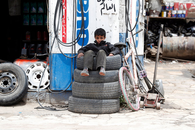 A child worker sits on tires as he waits for customers at a workshop in Sanaa, Yemen, 21 April 2020. (Photo by Yahya Arhab/EPA/EFE)