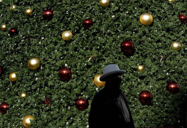 A man walks past the large Macy's Tree at Union Square in San Francisco, November 23, 2012. (Photo by Jeff Chiu/Associated Press)