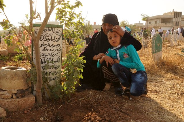 A woman holds her grandson as she prays near her son's grave at the Martyrs' cemetery on the first day of Eid al-Adha in the town of Dael near Deraa, Syria September 24, 2015. (Photo by Alaa Al-Faqir/Reuters)
