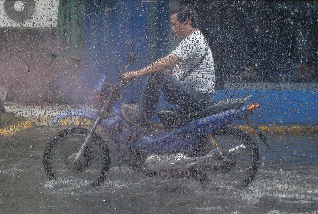Raindrops are seen on glass as a man riding his motorbike through a flooded street after a brief but heavy rainfall in Manila, Philippines, Tuesday, August 2, 2016. Many low-lying areas in the city are flood prone during heavy rains. (Photo by Aaron Favila/AP Photo)