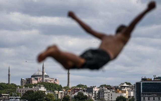 A man dives into the Bosphorus at Karakoy district on July 14, 2020 as Hagia Sophia is seen in the backround in Istanbul. Turkey's Hagia Sophia could open to visitors outside prayer times and its Christian icons will remain, religious officials said on Tuesday, after a court ruling paved the way for it to become a mosque. (Photo by Ozan Kose/AFP Photo)