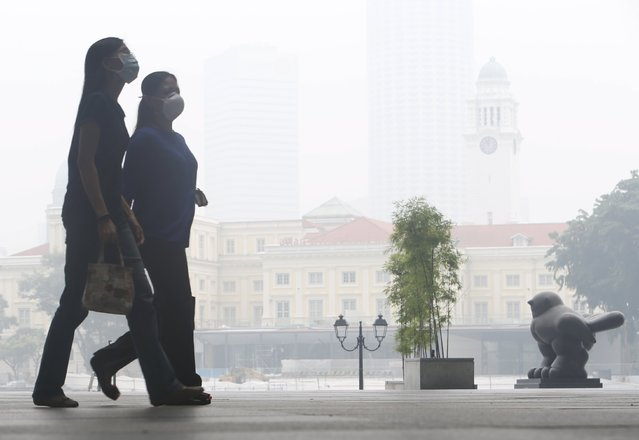 Office workers wearing masks walk during lunch hour at the central business district in Singapore September 29, 2015. (Photo by Edgar Su/Reuters)