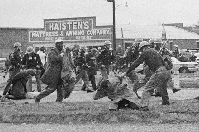 In this March 7, 1965, file photo, a state trooper swings a billy club at John Lewis, right foreground, chairman of the Student Nonviolent Coordinating Committee, to break up a civil rights voting march in Selma, Ala. Lewis sustained a fractured skull. Lewis, who carried the struggle against racial discrimination from Southern battlegrounds of the 1960s to the halls of Congress, died Friday, July 17, 2020. (Photo by AP Photo/File)