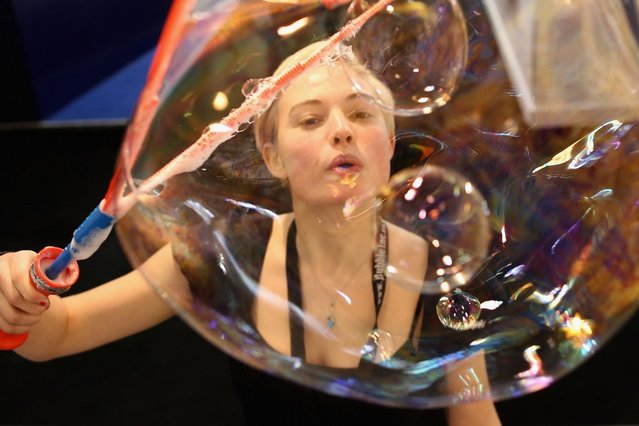 A woman on a trade stand blows bubbles during the 2013 London Toy Fair at Olympia Exhibition Centre on January 22, 2013 in London, England. The annual fair which is organised by the British Toy and Hobby Association, brings together toy manufacturers and retailers from around the world.  (Photo by Dan Kitwood)