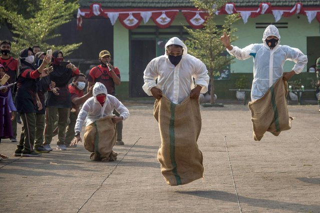 Indonesian soldiers wearing facemasks and personal protective equipment take a part in a sack race during games to celebrate ahead of the country's 75th Independence Day in Surabaya, East Java on August 14, 2020. Indonesia will mark its 75th Independence Day on August 17. (Photo by Juni Kriswanto/AFP Photo)