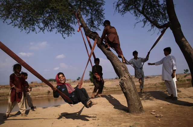 Pakistani Dawlat Gul, 7, third left, enjoys playing on a swing along with other children on the outskirts of Islamabad, Pakistan, Friday, July 13, 2012. (Photo by Muhammed Muheisen/AP Photo)