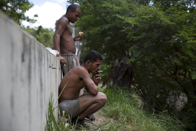 "In this December 7, 2017 photo, Felix Diaz smokes a cigarette next to Angel Villanueva eating a piece of bread as they take a break from scraping the bottom of the polluted Guaire River in search of gold and anything of value to sell, in Caracas, Venezuela. ""Working in the Guaire isn't easy. It's hard"", said 25-year-old Villanueva. ""When it provides, it provides. When it takes, it takes your life"", referring to flash flooding. Diaz, a former security guard who lives with his sister, said he started searching the river nine months ago. (Photo by Ariana Cubillos/AP Photo)"