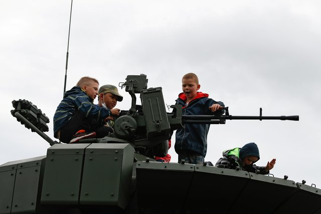 "Children play atop a military vehicle that is on display during the International military-technical forum ""Army-2020"" at Alabino range in Moscow Region, Russia, August 24, 2020. (Photo by Evgenia Novozhenina/Reuters)"