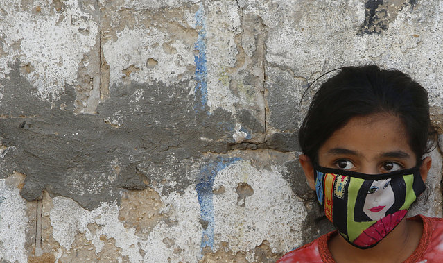 A Palestinian girl wear a face mask during a lockdown imposed following the discovery of coronavirus cases in the Gaza Strip, Thursday, August 27, 2020. On Wednesday Gaza's Hamas rulers extended a full lockdown in the Palestinian enclave for three more days as coronavirus cases climbed after the detection this week of the first community transmissions of the virus in the densely populated, blockaded territory. (Photo by Hatem Moussa/AP Photo)