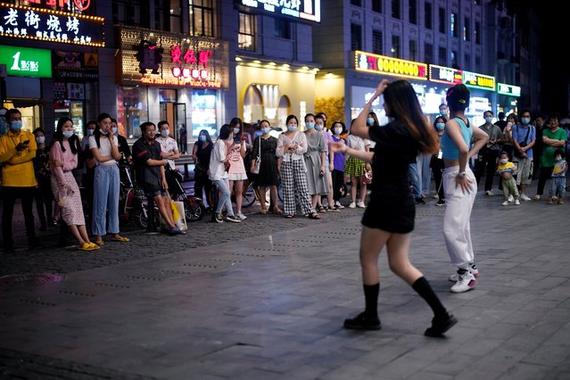 People wearing protective masks watch as women dance on the street, following the coronavirus disease (COVID-19) outbreak in Wuhan, Hubei province, China on September 2, 2020. (Photo by Aly Song/Reuters)