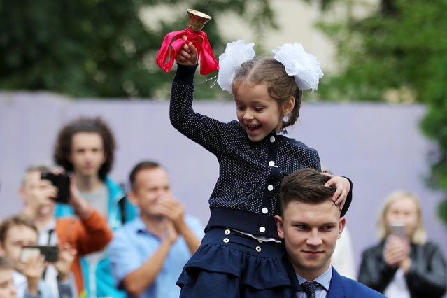 A first-grade student rings the first bell during a ceremony marking the beginning of a new academic year at Gymnasium 23 in Minsk, Belarus on September 1, 2020. (Photo by Sergei Bobylev/TASS)