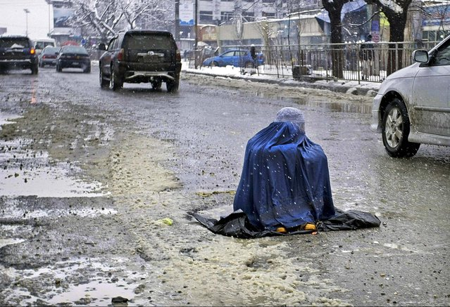 A woman sits in a street begging for money from motorists in Kabul, Afghanistan, on February 4, 2013. (Photo by Musadeq Sadeq/Associated Press)