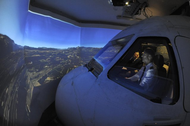 Igor Perne (R), 53, an electronic engineer and a member of the International Virtual Aviation Organisation (IVAO), and fellow virtual pilot Franc Lavric fly on a virtual flight in a flight simulator in Nova Vas November 13, 2014. (Photo by Srdjan Zivulovic/Reuters)