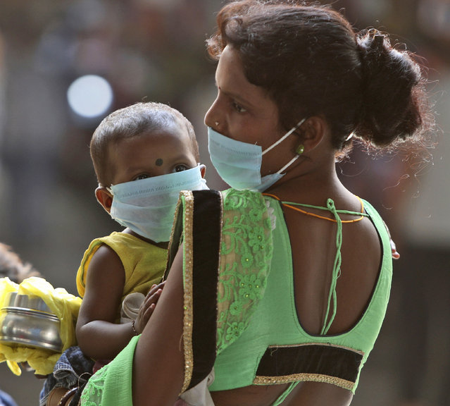 A woman wearing a face mask as a precaution against the coronavirus carries a child and waits for transportation at a bus station in Jammu, India, Friday, September 11, 2020. Results of India's first nationwide study of prevailing coronavirus infections has found that for every confirmed case detected in May, authorities were missing between 82 and 130 others. At the time, India had confirmed around 35,000 cases and over 1,000 deaths. The study released Thursday shows 6.4 million people were likely infected. (Photo by Channi Anand/AP Photo)