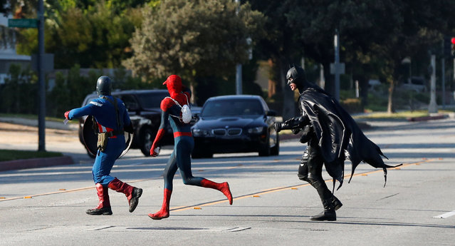 People dressed like comic book characters Captain America, Spider-Man and Batman run across the street in Pasadena, California U.S., August 27, 2016. (Photo by Mario Anzuoni/Reuters)