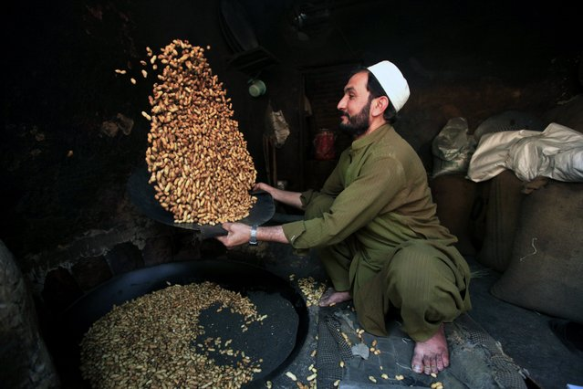 A Pakistani vendor prepares peanuts for sale on a roadside in Peshawar, Pakistan, 01 January 2018. After a good raining season the sales of dry fruits flourish in the country. Tourists from all over Pakistan come to Peshawar to purchase dry fruits along with other items because of price differences between different parts of the country. (Photo by Bilawal Arbab/EPA/EFE)