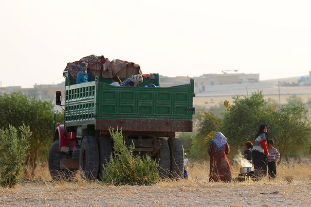 Syrians that fled recent fighting in Aleppo cook near a truck in the southern countryside of Aleppo, Syria October 19, 2015. Fighting in Syria has displaced 35,000 people from Hader and Zerbeh on the southwestern outskirts of the city of Aleppo in the past few days, the U.N. Office for the Coordination of Humanitarian Affairs (OCHA) said on Monday. (Photo by Ammar Abdullah/Reuters)