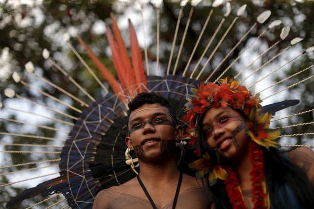 A indigenous man from the Xambioa tribe poses for photos with an indigenous girl from the Pataxo tribe as they arrive to participate in the I World Games for Indigenous People in Palmas, Brazil, October 20, 2015. (Photo by Ueslei Marcelino/Reuters)