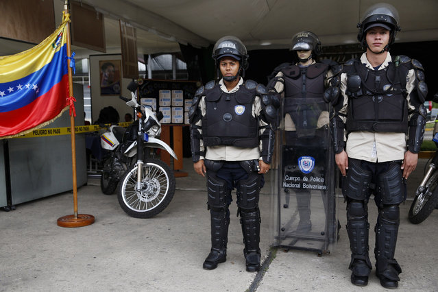"Venezuela's national police officers Bello (R) and Bogado pose for a picture with their riot equipment, next to a mannequin in uniform during a government Christmas fair in Caracas November 13, 2014. In Venezuela, no firearms are to be carried or used for control of peaceful demonstrations. When there is a threat to order, and other methods of conflict resolution have failed, police are instructed to warn crowds or demonstrators that there will be a ""progressive, differentiated use of force"". (Photo by Carlos Garcia Rawlins/Reuters)"