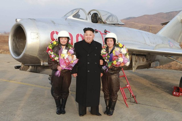 North Korean leader Kim Jong Un poses for pictures with female pilots as he provides field guidance to the flight drill of female pilots of pursuit planes of the KPA Air and Anti-Air Force in this undated photo released by North Korea's Korean Central News Agency (KCNA) in Pyongyang November 28, 2014. (Photo by Reuters/KCNA)