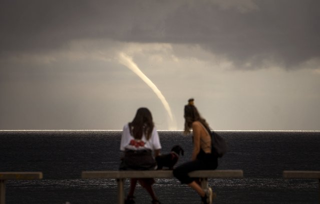 People look at a funnel cloud formed near the beach in Barcelona, Spain, Monday, September 21, 2020. (Photo by Emilio Morenatti/AP Photo)