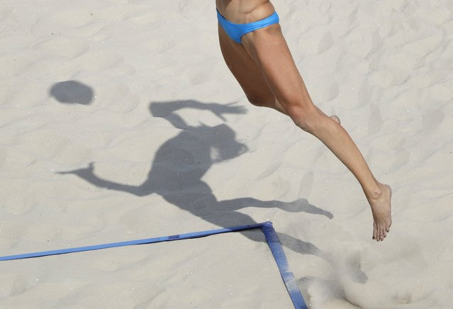 Russia's Ekaterina Birlova casts a shadow on the sand as she serves to Poland during a women's beach volleyball match at the 2016 Summer Olympics in Rio de Janeiro, Brazil, Tuesday, August 9, 2016. (Photo by Marcio Jose Sanchez/AP Photo)