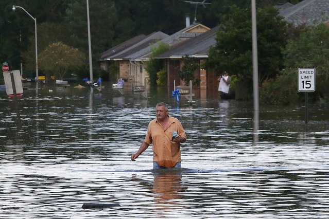 A man wades through a flooded street in Ascension Parish, Louisiana, U.S., August 15, 2016. (Photo by Jonathan Bachman/Reuters)