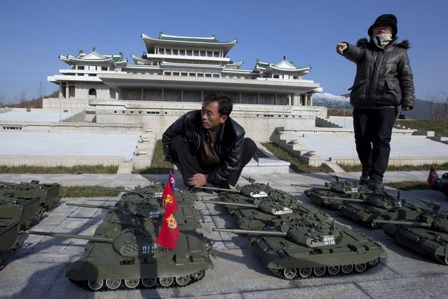 North Korean workers arrange model tanks with the North Korean People's Army flags in a parade formation in front of a replica of the Grand People's Study House at the Pyongyang Folk Park, on November 18, 2012. The park, which spans Korean history from prehistoric to modern times, opened in September, 2012 after three years of construction by the North Korean soldiers. (Photo by Ng Han Guan/AP Photo)