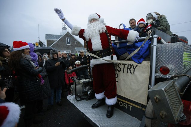 A man dressed as Santa Claus waves from the back of an antique fire truck after arriving on a lobster boat for the town's Tree Lighting ceremony in Rockport, Massachusetts December 6, 2014. (Photo by Brian Snyder/Reuters)