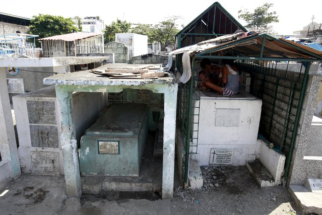 A family takes shelter from the sun in a mausoleum, which they have made their home, inside the Manila South Public Cemetery in Pasay City, metro Manila October 30, 2015. (Photo by Romeo Ranoco/Reuters)