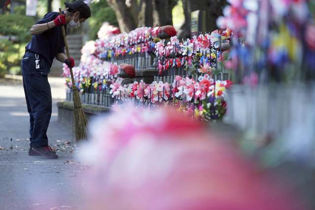 "An employee wearing a protective mask to help curb the spread of the coronavirus sweeps near pinwheels whirl in the breeze at rows of small stone statues of ""jizo"" representing the unborn children at a temple in Tokyo Thursday, October 29, 2020. The Japanese capital confirmed more than 220 new coronavirus cases on Thursday. (Photo by Eugene Hoshiko/AP Photo)"