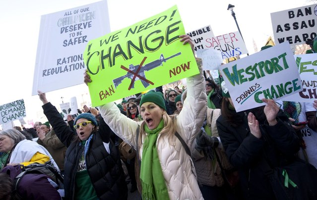 Demonstrators yell and hold up signs during a rally at the Capitol in Hartford, Conn., Thursday, February 14, 2013. Thousands of people turned out to call on lawmakers to toughen gun laws in light of the December elementary school shooting in Newtown that left 26 students and educators dead. (Photo by Jessica Hill/AP Photo)