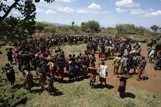 Pokot girls and adults stand in a circle during an initiation ceremony of over a hundred girls passing over into womanhood, about 80 km (50 miles) from the town of Marigat in Baringo County December 6, 2014. (Photo by Siegfried Modola/Reuters)