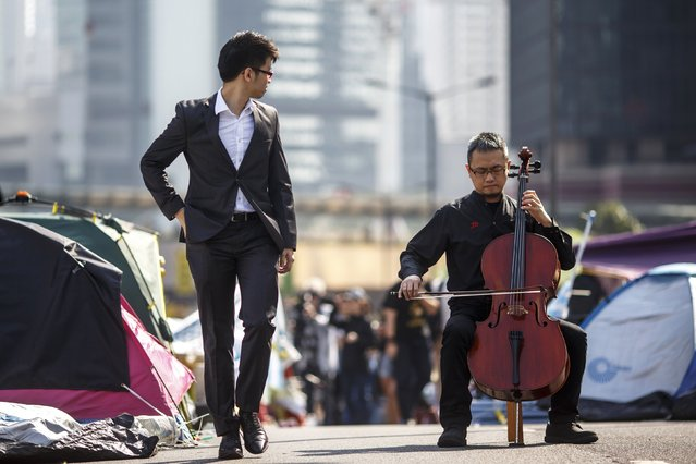 David Wong, a 41-year-old cellist, performs on a vehicle bridge filled with tents set up by pro-democracy protesters at the financial Central district in Hong Kong December 9, 2014. Hong Kong's High Court has ordered the main protest sites that have choked the financial city for more than two months to be cleared, building up to a final showdown on Thursday between pro-democracy activists and authorities backed by Beijing. (Photo by Athit Perawongmetha/Reuters)