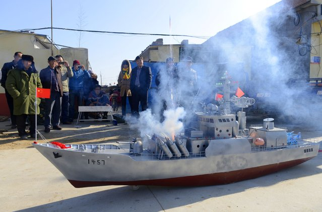 Residents look on as a mocked missile, made of gunpowder, fires from a homemade replica of a destroyer vessel made by retired fishboat captain Guo Changhai, during a test run in Xiaojia village of Rizhao, Shandong province, December 13, 2014. (Photo by Reuters/China Daily)