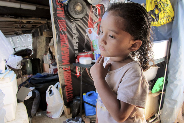 In this October 7, 2015 photo, Keioleen Helly, 3, stands inside her family's sidewalk shelter in Honolulu. The family was packing up belongings to take to a storage unit two days before the city planned to clear their block of the homeless encampment, hoping to get a ride to the storage unit from a volunteer. (Photo by Cathy Bussewitz/AP Photo)