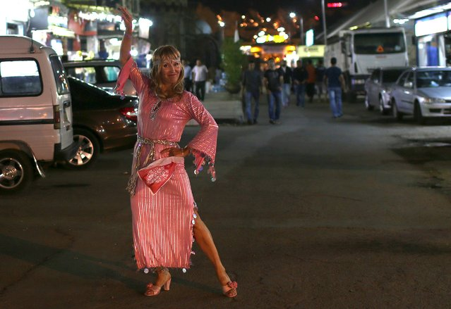 A tourist reacts as she walks wearing a traditional dance costume near bazaars in the Red Sea resort of Sharm el-Sheikh, Egypt November 10, 2015. The fallout from the crash of a Russian Metrojet passenger plane in Egypt's Sinai Peninsula could slash tourism income from Sharm al-Sheikh by half, the head of the region's travel agents' association said on Tuesday. (Photo by Asmaa Waguih/Reuters)