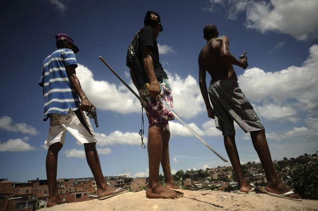 Brazilian drug gang members pose with weapons atop a hill overlooking a slum in Salvador, Bahia State, April 11, 2013. (Photo by Lunae Parracho/Reuters)