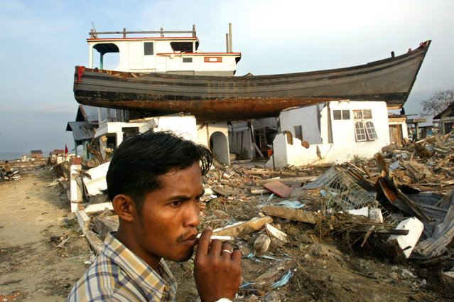 In this February 17, 2005 file photo, an Acehnese man smokes a cigarette near a house on which a fishing boat landed after it was swept away by tsunami in Banda Aceh, Aceh province, Indonesia. (Photo by Dita Alangkara/AP Photo)