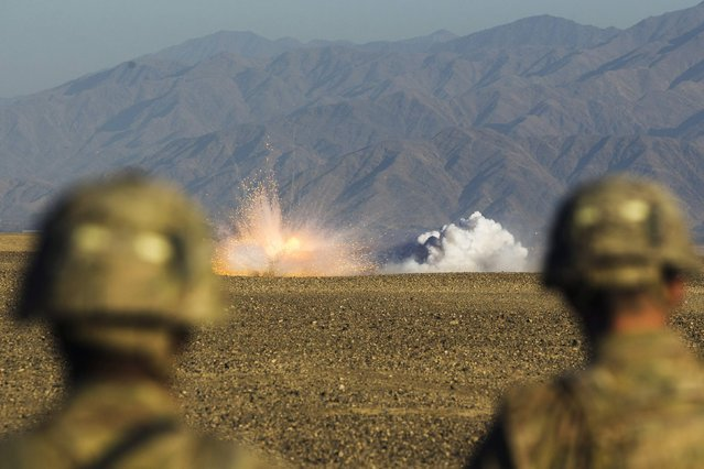 U.S. soldiers in Dragon Company of the 3rd Cavalry Regiment watch rounds explode downrange during a mortar exercise near forward operating base Gamberi in the Laghman province of Afghanistan December 26, 2014. (Photo by Lucas Jackson/Reuters)