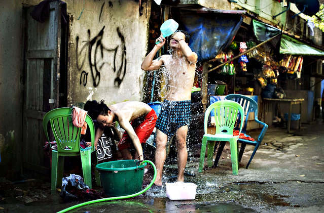 """People shower in a street in Yangon on November 12, 2015. US President Barack Obama congratulated Myanmar for holding """"free and fair"""" polls, a minister said, as the government and army chief promised a smooth transition of power as Aung San Suu Kyi's party tip-toed towards an election victory. (Photo by Nicolas Asfouri/AFP Photo)"""